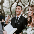 bride and groom smiling while officiant reads out of bible