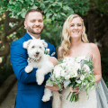 bride holding flowers with groom holding white fluffy dog in front of tree